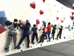 Kids traversing a wall together at camp